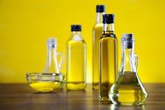Olio di oliva e bottiglie delle olive su priorità bassa gialla Fotografie Stock