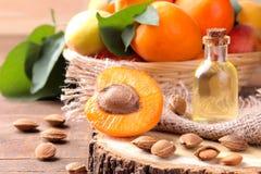 Olio di semi dell'albicocca accanto alle albicocche fresche su un fondo di legno marrone fotografia stock libera da diritti
