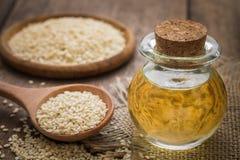 Olio di sesamo in barattolo e semi di sesamo di vetro sul cucchiaio di legno Immagini Stock Libere da Diritti