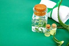 Olio di vera dell'aloe in bottiglia di vetro ed asciugamano per la stazione termale Immagine Stock