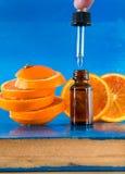 Olio essenziale con le fette, la bottiglia ed il contagoccia arancio Immagini Stock Libere da Diritti