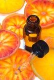 Olio essenziale dell'arancia in bottiglia ambrata con le arance rosse fotografia stock libera da diritti