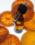 Olio essenziale dell'arancia in bottiglia ambrata con le arance rosse Fotografie Stock
