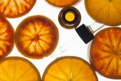 Olio essenziale dell'arancia in bottiglia ambrata con le arance rosse Immagini Stock