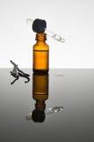 Olio essenziale della vaniglia in bottiglia ambrata con i baccelli di vaniglia e il dro Immagine Stock
