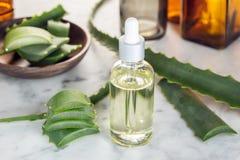 Olio essenziale della vera dell'aloe Olio di vera dell'aloe sulla bottiglia di vetro con il contagoccia fotografie stock