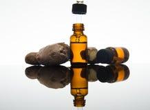 Olio essenziale dello zenzero in bottiglia ambrata con la radice ed il contagoccia dello zenzero fotografia stock libera da diritti