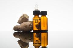 Olio essenziale dello zenzero in bottiglia ambrata con la radice ed il contagoccia dello zenzero Fotografie Stock