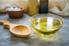 Olio liquido della noce di cocco MCT in ciotola di vetro rotonda con il cucchiaio di legno e immagine stock libera da diritti