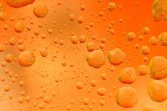Olio misto in acqua su un fondo giallo arancione e dorato variopinto Fotografato nella fine su con DOF basso Foto presa: immagine stock libera da diritti