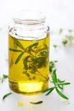 Olio profumato con rosmarino e le erbe fresche immagini stock