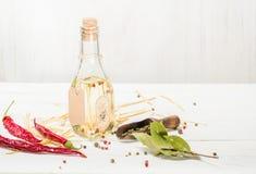 Olio vegetale in una bottiglia con i condimenti e le spezie su un fondo di legno bianco Immagini Stock Libere da Diritti