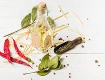 Olio vegetale in una bottiglia con i condimenti e le spezie su un fondo di legno bianco Immagine Stock Libera da Diritti