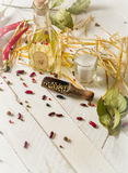 Olio vegetale in una bottiglia con i condimenti e le spezie su un fondo di legno bianco Fotografia Stock