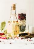 Olio vegetale in una bottiglia con i condimenti e le spezie su un fondo di legno bianco Immagine Stock