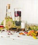Olio vegetale in una bottiglia con i condimenti e le spezie su un fondo di legno bianco Fotografie Stock