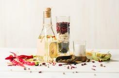 Olio vegetale in una bottiglia con i condimenti e le spezie su un fondo di legno bianco Fotografia Stock Libera da Diritti