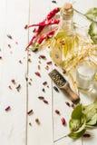 Olio vegetale in una bottiglia con i condimenti e le spezie su un fondo di legno bianco Immagini Stock