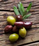Oliv fattar och oliv på den gamla trätabellen royaltyfri bild
