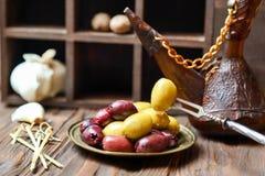 Oliv i brons platel på ett träköksbord fotografering för bildbyråer