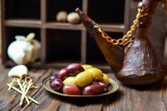 Oliv i brons platel på ett träköksbord royaltyfri fotografi