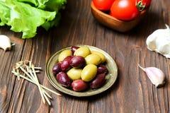 Oliv i brons plattan på köksbordet arkivbild