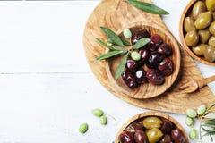 Oliv i träbunkar dekorerade med den nya olivträdfilialen på den vita bästa sikten för köksbordet royaltyfri bild