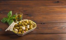 Oliv och oljor med basilika och ett skottexponeringsglas royaltyfria foton