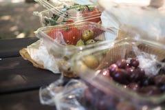 Oliv och tomater på en picknicktabell, i plast- behållare royaltyfri fotografi