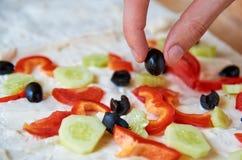 Oliva nera in una mano con le verdure tagliate sulla fine vaga del fondo su Fotografia Stock