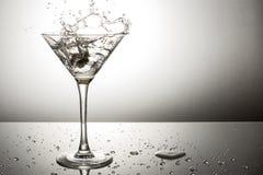 Olive éclaboussant sur martini Photographie stock libre de droits