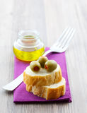 Olive and baguette. Fresh green olive on baguette Royalty Free Stock Image