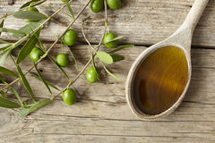 Olive branch and a spoon full of oil Stock Photo