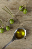 Olive branch and a spoon full of oil Royalty Free Stock Photo