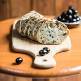 Olive bread. Slices of black olive bread on a wooden table stock images