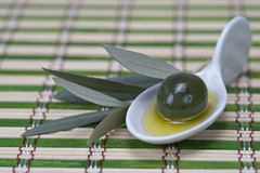 Olive in a china spoon Royalty Free Stock Images