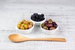 Olive in ciotole ed in un cucchiaio di legno Fotografie Stock