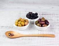 Olive in ciotole ed in un cucchiaio di legno Immagine Stock