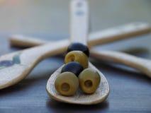 Olive con il cucchiaio d'annata sul primo piano scuro della tavola immagine stock libera da diritti