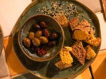 Olive con le fette croccanti casalinghe del pane e semi di sesamo sul piatto dell'aperitivo fotografia stock