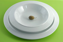 Olive diet!. A little bitter olive lays in a stilish porcelain plate Royalty Free Stock Photos