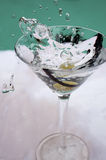 Olive drop in martini Royalty Free Stock Images