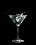 Olive dropped in a cocktail glass with liquid. Olive dropped in cocktail glass with liquid making a a big splash. Isolated on black Royalty Free Stock Images