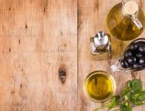 Olive e bottiglie e tazza di olio d'oliva sane con prezzemolo Immagini Stock