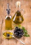 Olive e bottiglie e tazza di olio d'oliva sane con prezzemolo Immagine Stock