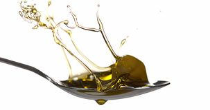 Olive falling into olive oil against white background stock footage
