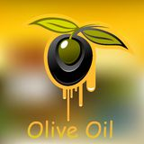 Olive fruit and dripping olive oil. Black olive fruit with pointed green leaves dripping natural olive oil on blurred background Royalty Free Stock Photos