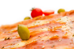 Olive garnish on pizza. With blurry cherry tomato in the background Royalty Free Stock Photo