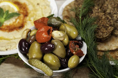 Olive Medley. Olives, pickles and peppers in a white bowl with humus and felafels Stock Photos