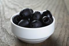 Olive nere dalla latta in ciotola sulla tavola Fotografia Stock